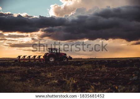 Tractor plowing the fields in the countryside by sunset. Agricultural tractor plowing the field. Red Tractor with plow. Sunset over the autumn field. Сток-фото ©