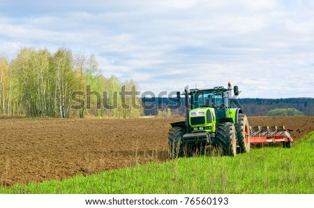 Tractor plows a field in the spring accompanied by rooks