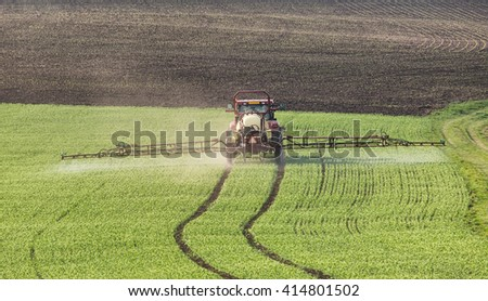 Tractor pours fertilizer in agriculture field