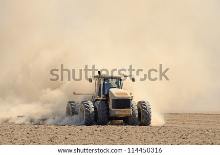tractor pulling a disc soil finisher implement to smooth the soil after tillage and plowing