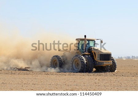 tractor pulling a disc soil finisher implement to smooth the soil after tillage and plowing - stock photo