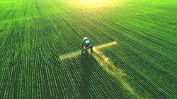 Tractor spray fertilizer on green field drone high angle view, agriculture background concept.