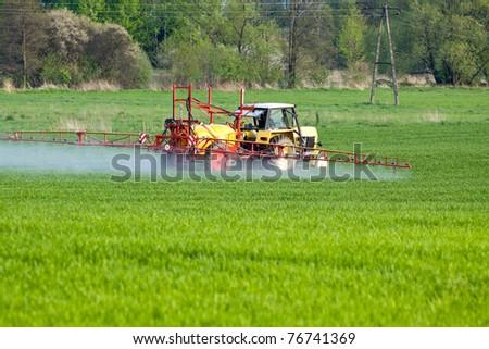 Tractor spraying a crop field on farm