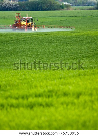 Tractor spraying a green field on farm - stock photo