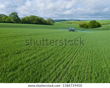 Tractor spraying crop in green farm fields with pesticide stock photo