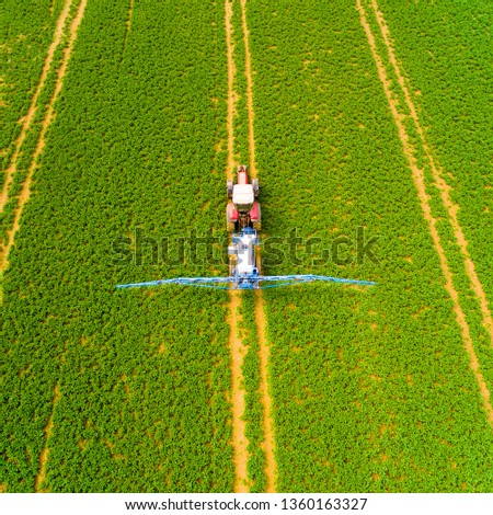 Tractor spraying herbicides on rapeseed field. Dangerous chemicals in agriculture. Sustainable development and renewable resources. Aerial view to agricultural work.