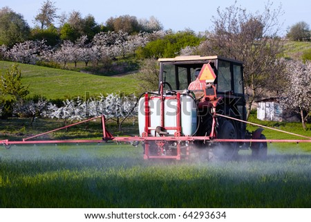 Tractor spraying on the field - stock photo