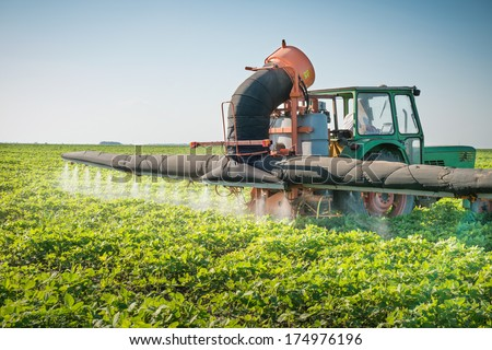 tractor spraying pesticides on soy bean