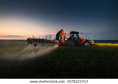 Tractor spraying pesticides on wheat field with sprayer at sunset