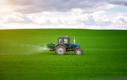 Tractor spreading potash fertilizer on green wheat field. Agriculture vehicle spraying field. Tractor spray fertilizers on green field, agriculture wallpaper. Farmer spreading potash fertilizers.
