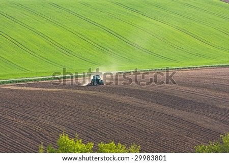 tractor throwing up dust on farmland
