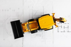 tractor toy on housing construction blueprint