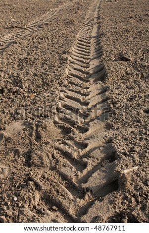 Tractor trail on the soil of an agricultural field