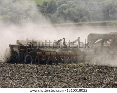 Tractor trailer cultivating ground creating dust