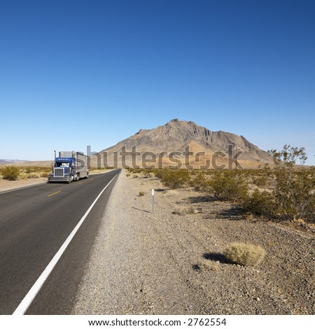 Tractor trailer driving on desert road with mountain in background.