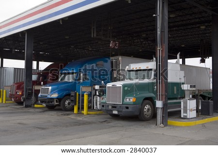 Tractor trailer rigs parked at truck stop for servicing