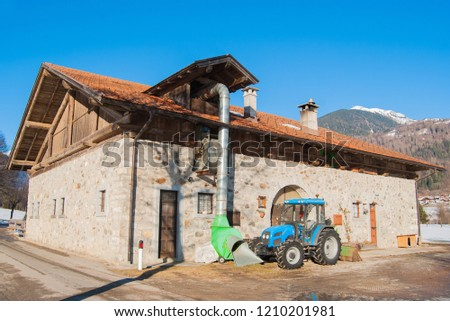 Tractor turned off close to a flours producing site with mountains on the background #1210201981