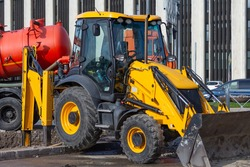 Tractor with a bucket stands at a construction site amid the construction of cranes and multi-storey buildings