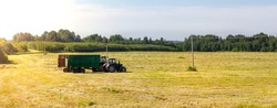 Tractor with a trailer in the field for agricultural work. Hay making, grassland. General plan, panorama. Copy space.