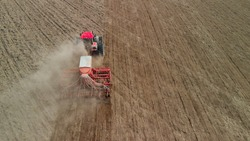 Tractor with a unit processes dusty soil on the prairie. Farmer sows in arid, lifeless steppes. Concept of risky agribusiness. Aerial view