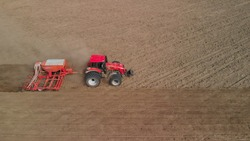 Tractor with a unit processes dusty soil on the prairie. Farmer sows in arid, lifeless steppes. Concept of risky agribusiness. Aerial side view