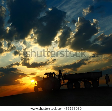 Tractor with cart over cloudy sunset background