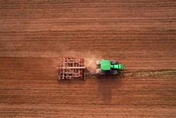 Tractor with disc cultivator Vaderstad on cultivating field. Agricultural tractor with Plough on Plowed and cultivation field. Soil Tillage and sowing seeds. Planting and Seeding Equipment.