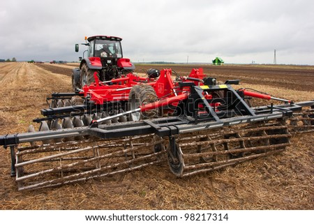 Tractor with equipment for land preparation in the fields in spring - stock photo