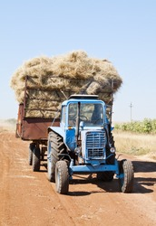 Tractor with hay cart on a field road