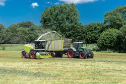 Tractor with loader wagon and forage harvester during the hay harvest