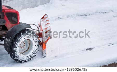 Tractor with snow plow blade clears road in city from fresh fallen snow. Snowplow removing snow on street after blizzard. Snowplow vehicle clears snowy road during blizzard. Snow clearing equipment