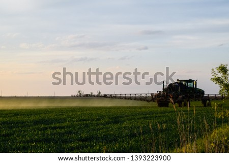 Tractor with the help of a sprayer sprays liquid fertilizers on young wheat in the field. The use of finely dispersed spray chemicals. #1393223900