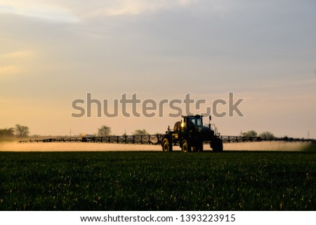 Tractor with the help of a sprayer sprays liquid fertilizers on young wheat in the field. The use of finely dispersed spray chemicals. #1393223915