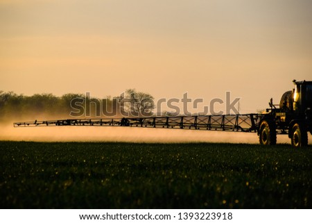 Tractor with the help of a sprayer sprays liquid fertilizers on young wheat in the field. The use of finely dispersed spray chemicals. #1393223918