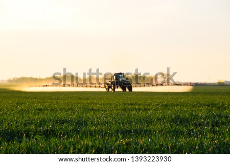 Tractor with the help of a sprayer sprays liquid fertilizers on young wheat in the field. The use of finely dispersed spray chemicals. #1393223930