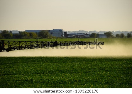 Tractor with the help of a sprayer sprays liquid fertilizers on young wheat in the field. The use of finely dispersed spray chemicals. #1393228178