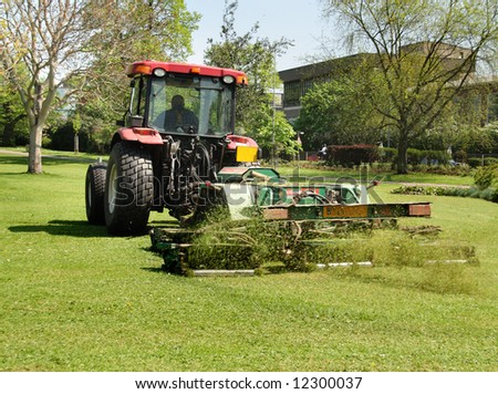 Tractor with trailer Mowing grass in a Public Park in England