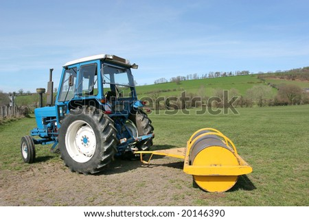 Tractor with yellow roller attached standing idle on farmland in rural countryside in spring. Farmers roll grass in spring to promote growth.