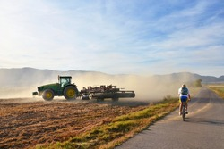 Tractor working on agricultural field in dust during calm autumn evening and bicycle
