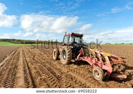 Tractors Plowing Field