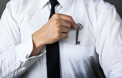 Trade secret concept. Close-up, businessman hides success key in shirt pocket
