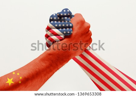 Trade war and rivalry. Two male hands competing in arm wrestling colored in China and America flags isolated on white studio background. Concept of economical and political relations, embargo. #1369653308