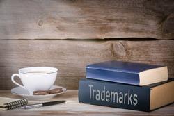 Trademarks. Stack of books on wooden desk