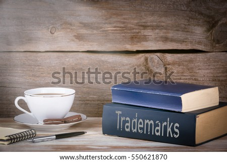 Trademarks. Stack of books on wooden desk