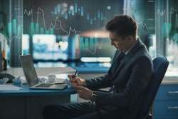 Trader, a player in the securities market on the Forex or Forbes. Elegant stylish successful in a suit in the office. On glass is large chart of the fall and increase in exchange rate of currencies