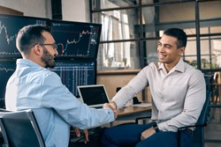 Trader manager making agreement hiring intern on full-time position shaking hands smiling cheerful sitting at office in front of monitors with trading data price flow candlestick charts