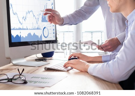 Traders discussing trading strategy for better profit and return on investment (ROI) by analyzing stock market and foreign exchange (forex) charts on computer screen #1082068391