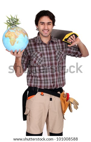 Tradesman holding a globe and saw - stock photo