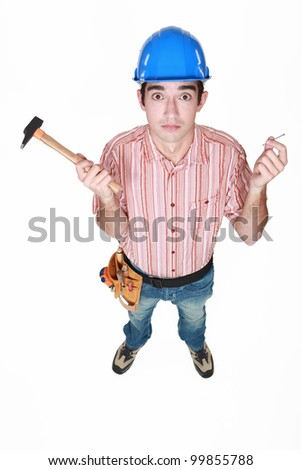 Tradesman holding a hammer and a nail