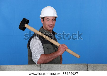 Tradesman holding a mallet and standing behind a low wall